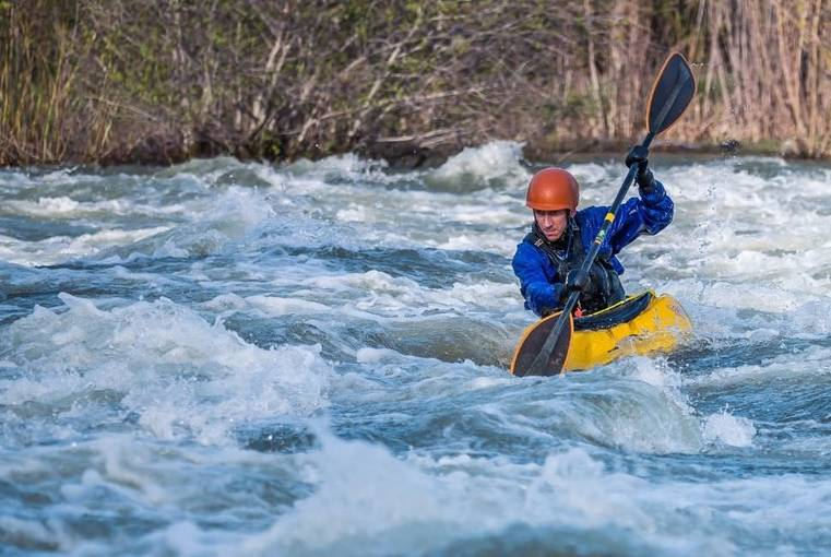 a man whitewater kayaking